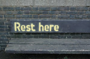 "A photo of a wooden bench with the words ""Rest here"" painted on its back, in front of a black brick wall."