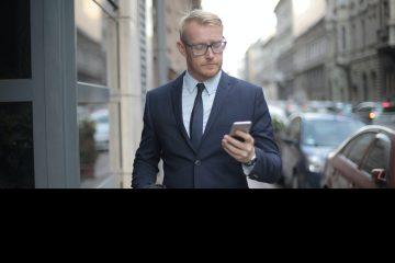 Meneer in pak kijkend naar zijn telefoon
