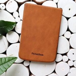 Duurzaam lezen e-reader: Pocketbook e-reader met congnac leren hoesje op een witte ondergrond met enkele groene bladeren