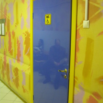 Синяя пластиковая дверь в больнице с желтым наличником