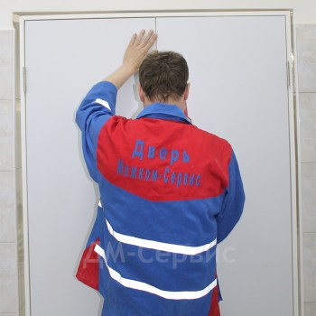 Установщик монтирует двухстворчатую пластиковую дверь