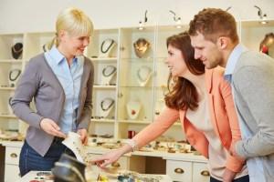 Verkäufer redet mit Paar im Schmuckladen