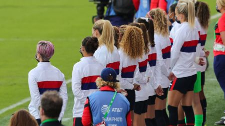 ORLANDO, FL - FEBRUARY 21: United States backup players, including Megan Rapinoe (L), stand for the United States National anthem against Brazil prior to the SheBelieves Cup at Exploria Stadium on February 21, 2021 in Orlando, Florida. (Photo by Alex Menendez/ Getty Images)