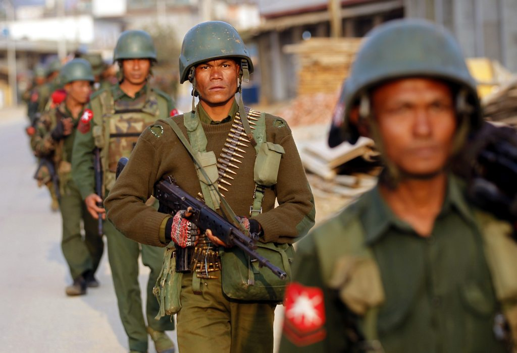 epa04622944 Armed military troops march as they clear the area at Chin Shwe Haw town of Kokang self-administered area, northern Shan State, Myanmar, 16 February 2015. Myanmar state media reported on 13 February 2015, that some 47 soldiers were killed, 73 wounded, and five vehicles were destroyed during clashes with Kokang rebels,who attacked military stations with the intent to capture the Laukkai, in a border area with China in northern Myanmar. Thousands of people living around Laukkai are fleeing as clashes outbreak continue in the area. EPA/LYNN BO BO