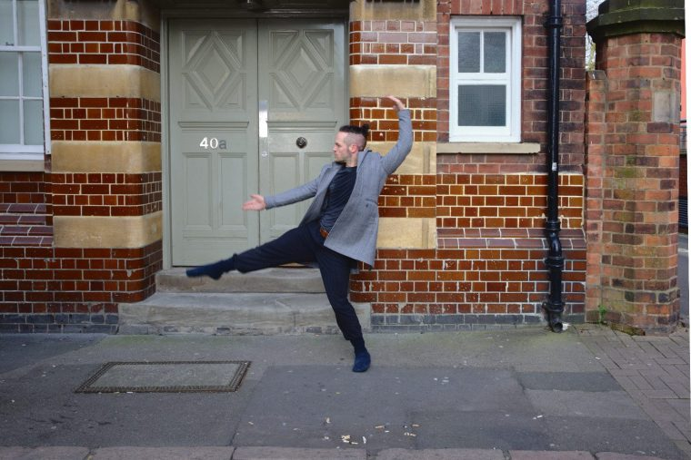 Ian Dolan, man contemporary dancing in the street in front of a door