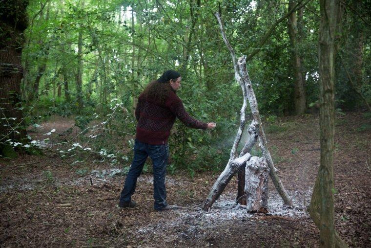 Matt Smith throws flour at a construction of branches