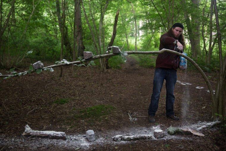 A stream of flour falls as Matt Smith covers bricks in flour balanced on a branch