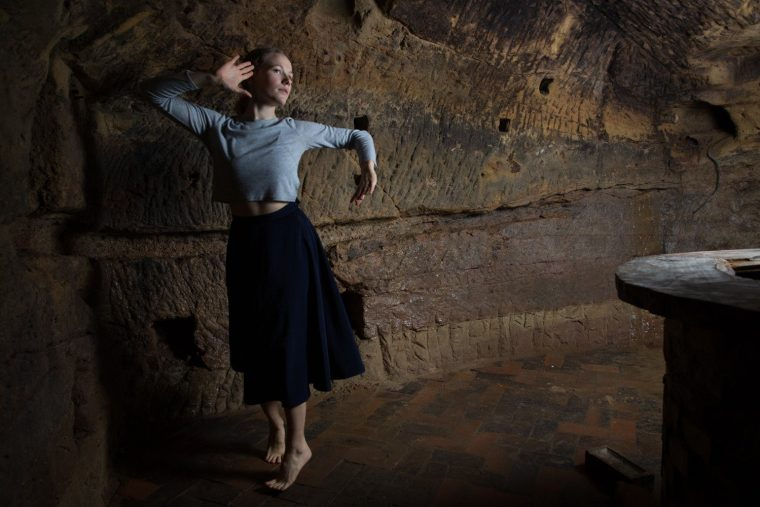 Amy Harris dancing dramatically in the caves of the Maltcross in Nottingham