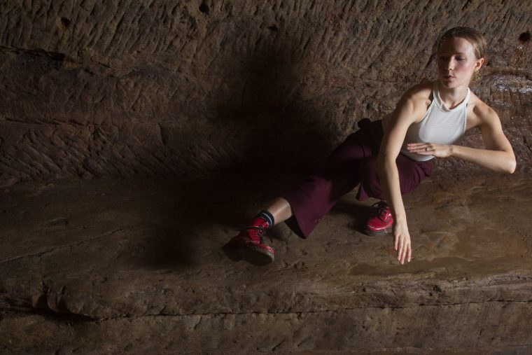 Amy Harris in red boots dancing in the caves of the Maltcross in Nottingham