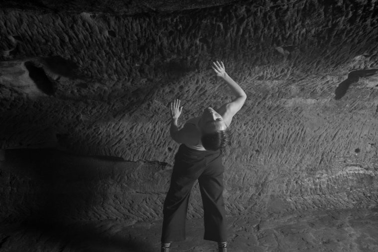 Amy Harris stretching while dancing in the caves of the Maltcross in Nottingham