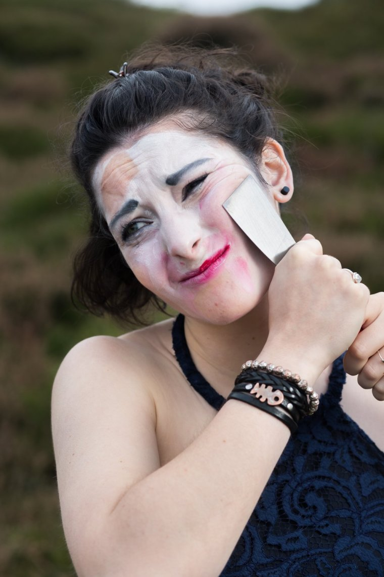 Emma Chatel removes her white painted makeup with a decorating tool