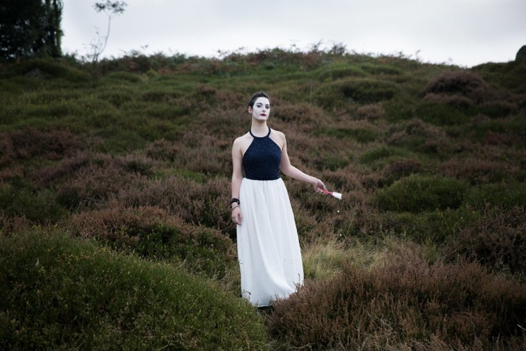 Emma Chatel dressed elegantly, with white painted makeup stands in grassland, with white paint dripping from a brush.