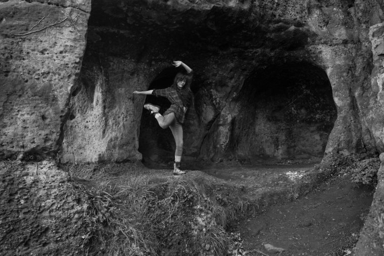 Black & white photo of Laura dancing at the cave entrance