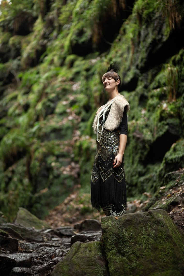 IsoElegant standing in a flapper dress with the green rocks of Lud's Church out of focus, behind.