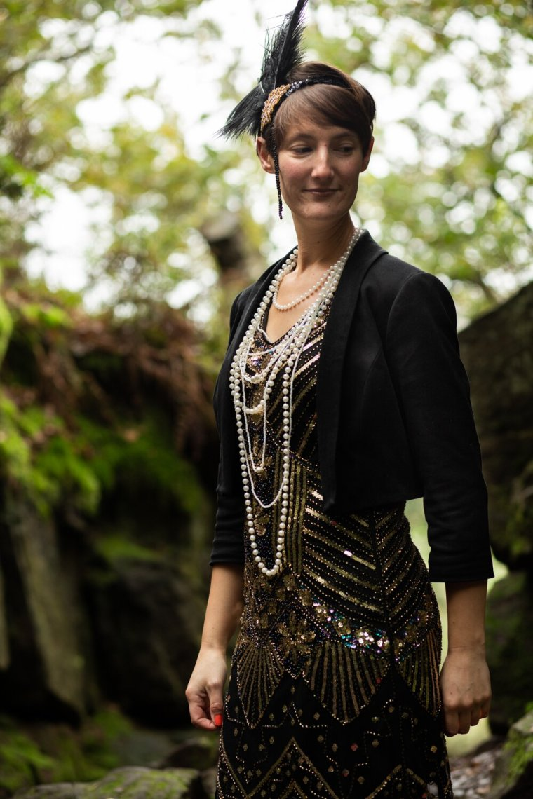 IsoElegant with trees behind, wearing a flappe dress and pearl necklaces.
