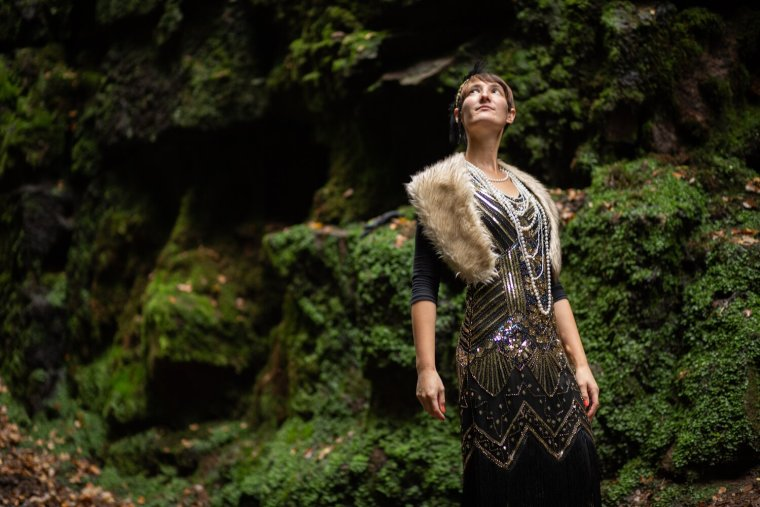 IsoElegant wearing a flapper dress, looking up at the rocks of Lud's Church.