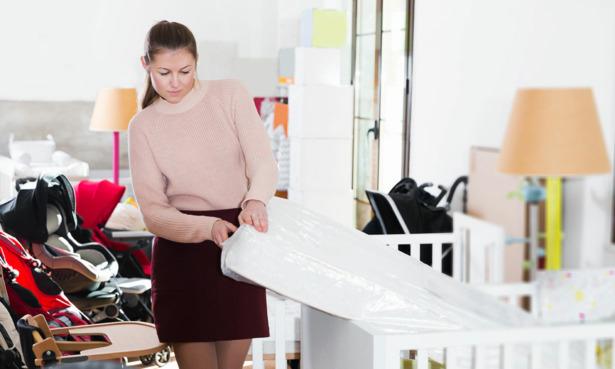 Woman inspecting a cot mattress