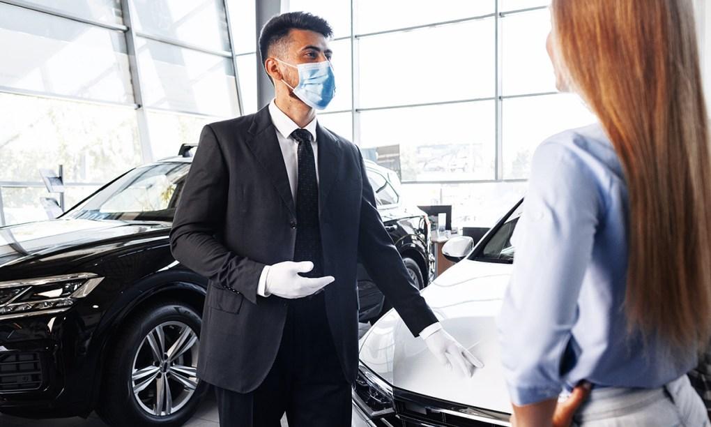 Masked car salesman & customer