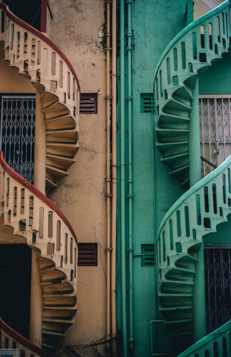beige and green concrete spiral stairs beside building