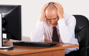 Front view studio shot of stressed middle aged businessman, fighting with problems, wearing formal attire. Head between arms, looking down. Sitting at desktop office computer.