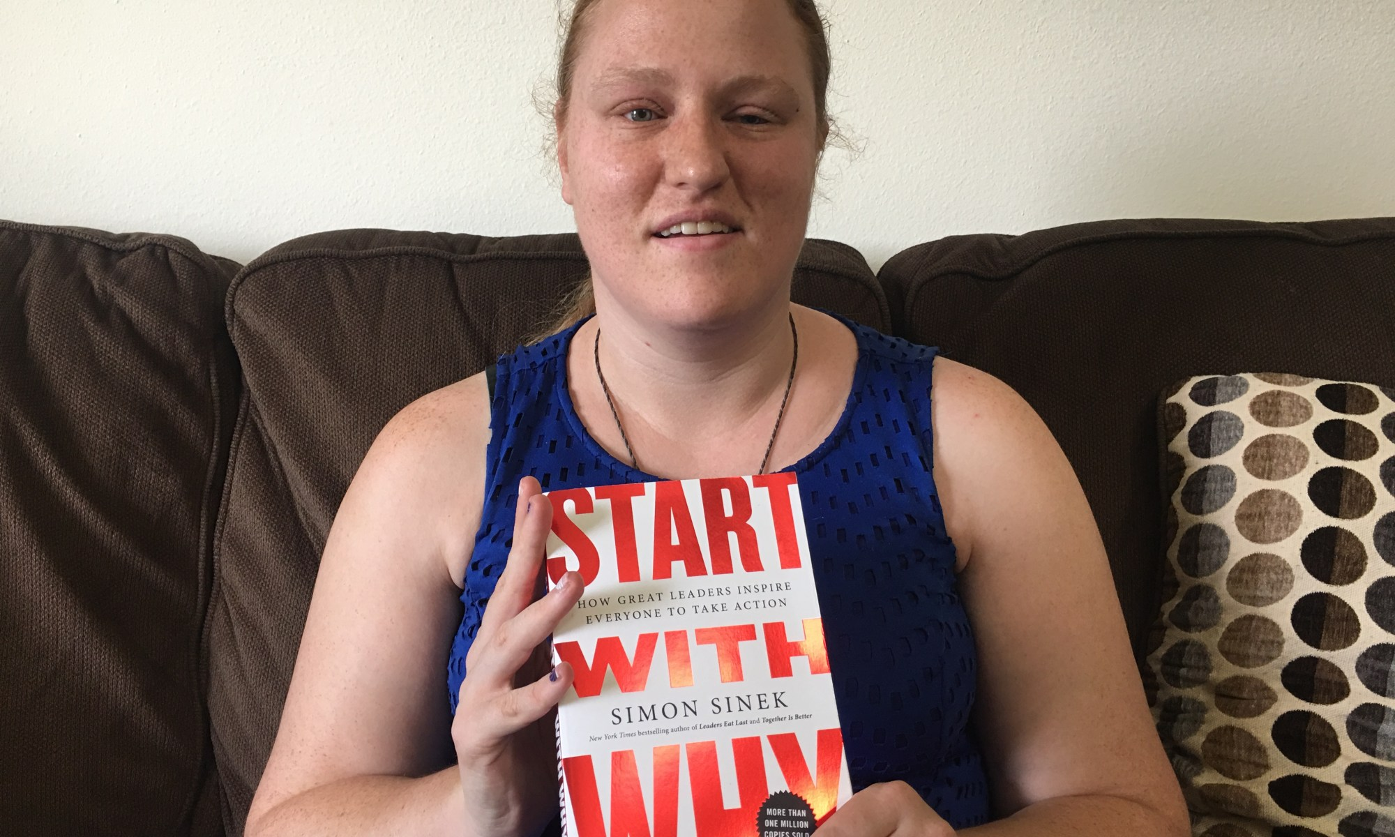 """Katie Corbett holds the book, """"Start With Why"""""""