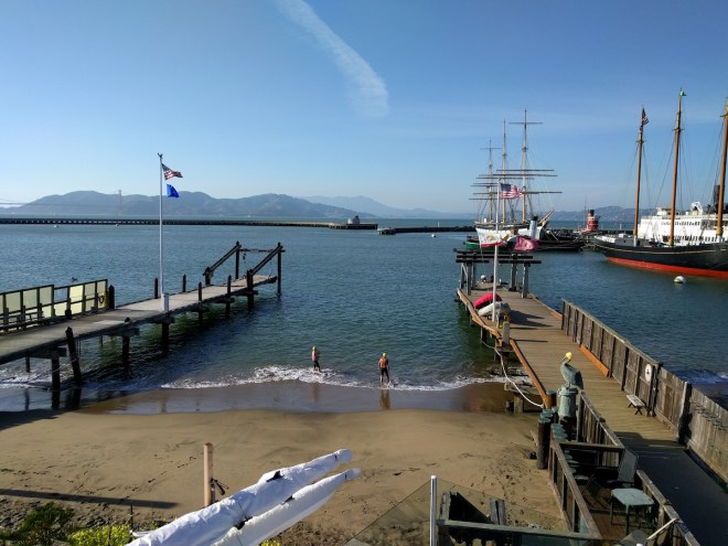 Picture of Aquatic Park cove showing two docks and a triple-masted schooner in the background