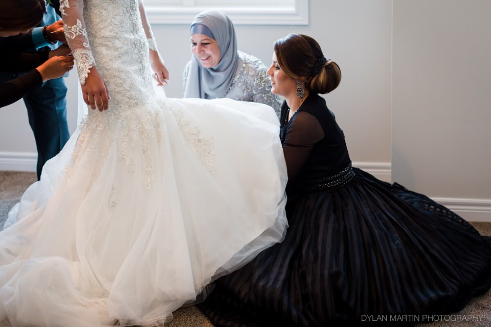 Bride wedding dress fitting preparation with sister and mother and father helping - Woodstock London Ontario Lebanese middle eastern Wedding and engagement photos - Dylan Martin Photography