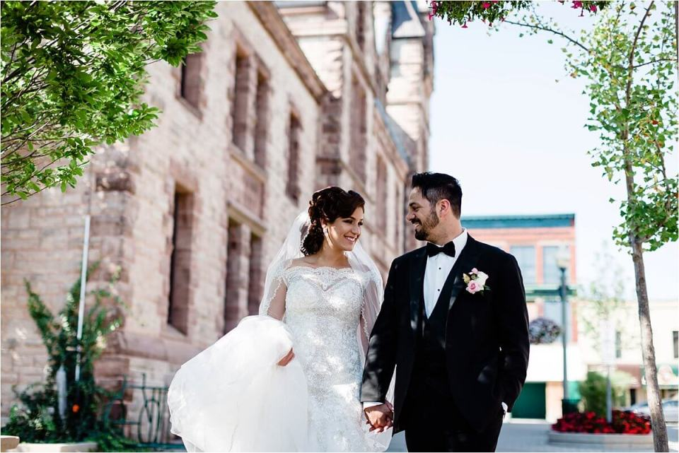 Bride and groom smiling at each other while they walk the street with trees and buildings - Woodstock London Ontario Lebanese middle eastern arab Wedding and engagement photos - Dylan Martin Photography