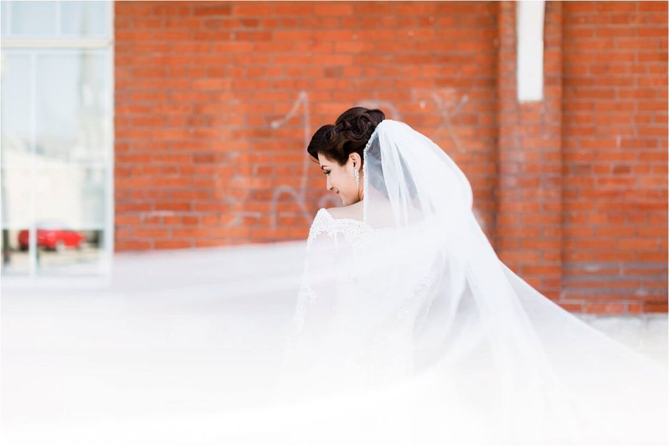 Bride with veil flowing behind in front of red brick wall - Woodstock London Ontario Lebanese middle eastern arab Wedding and engagement photos - Dylan Martin Photography