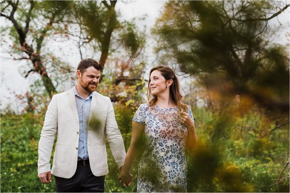 man in suit jacket holding hands with woman in a blue and white lace dress while walking in the forest - London Stratford Cambridge Woodstock Wedding Photographer by Dylan and Sandra of Dylan Martin Photography
