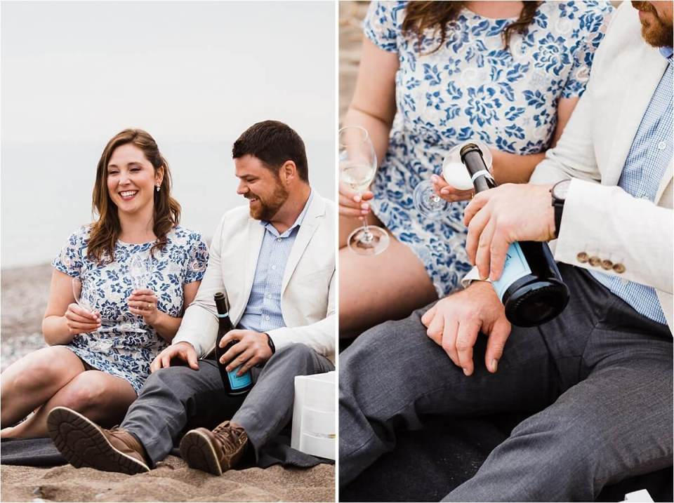 engaged couple sitting on the beach pouring a glass of wine - London Stratford Cambridge Woodstock Wedding Photographer by Dylan and Sandra of Dylan Martin Photography