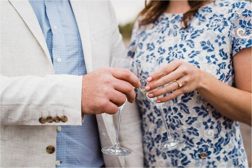 engaged couple celebrating with a glass of white wine - London Stratford Cambridge Woodstock Wedding Photographer by Dylan and Sandra of Dylan Martin Photography