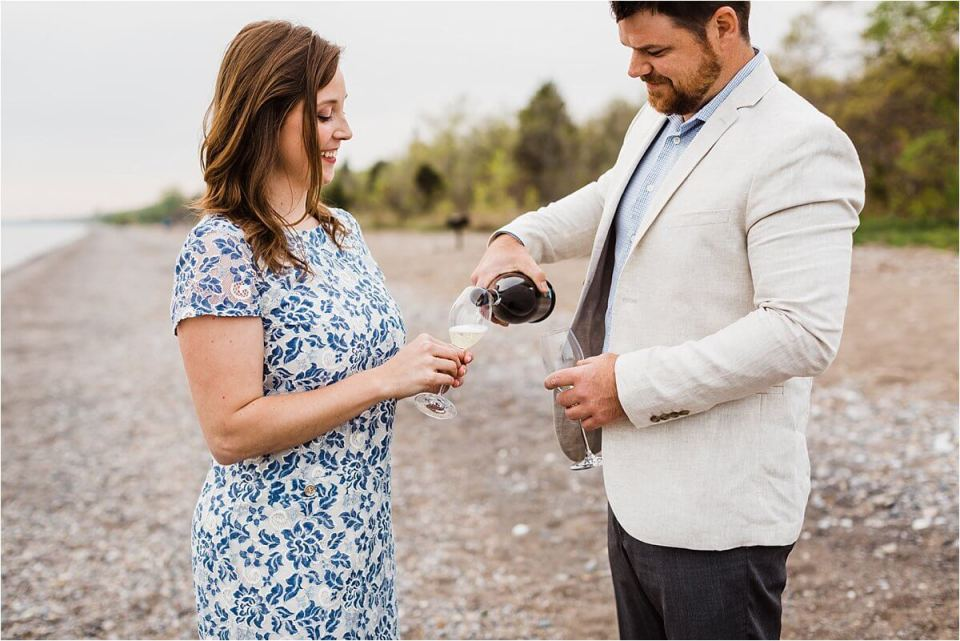 man pouring woman a glass of white wine on the beach - London Stratford Cambridge Woodstock Wedding Photographer by Dylan and Sandra of Dylan Martin Photography