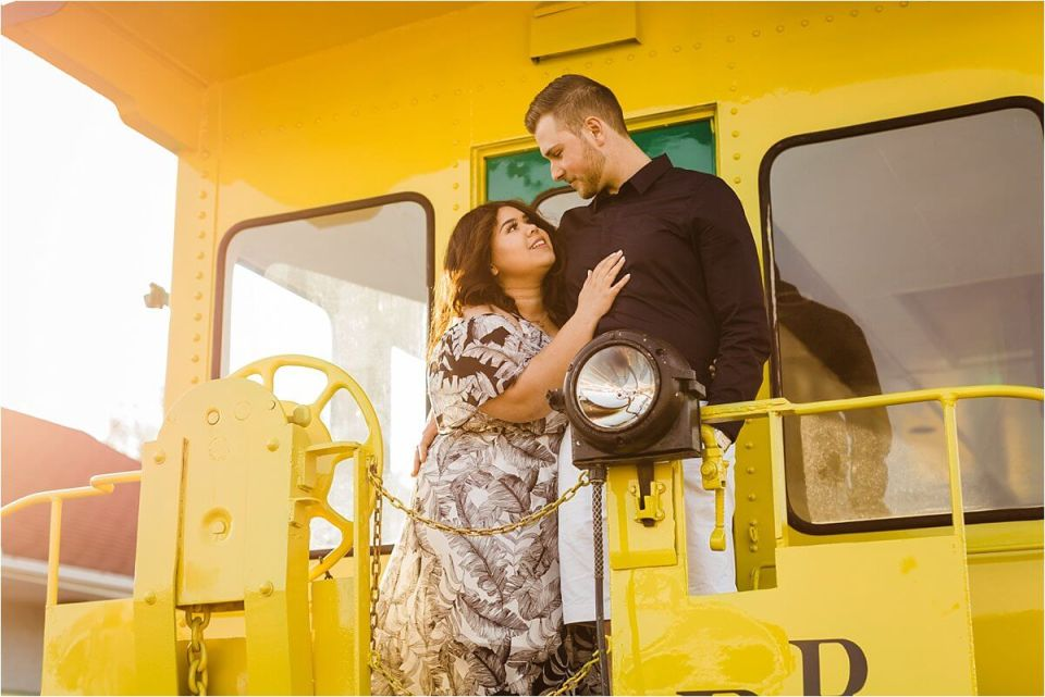 man and woman embracing on a yellow train at sunset - London Stratford Cambridge Woodstock Wedding Photographer by Dylan and Sandra of Dylan Martin Photography
