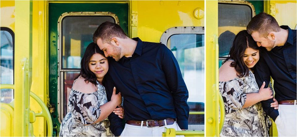 engaged couple cuddling on back of train caboose - London Stratford Cambridge Woodstock Wedding Photographer by Dylan and Sandra of Dylan Martin Photography