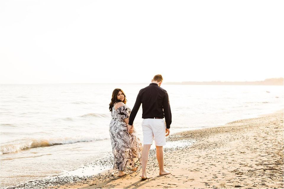 man and woman walking on the shore of the beach and woman looking back - London Stratford Cambridge Woodstock Wedding Photographer by Dylan and Sandra of Dylan Martin Photography