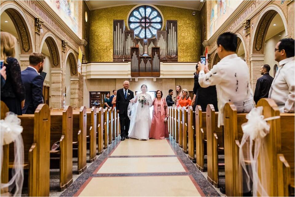 Bride walking down the aisle with her parents at her side at our lady of sorrows church in Toronto - Dylan and Sandra of Dyan Martin Photography for Weddings and Engagement candid photographer in London, Cambridge, Stratford and Woodstock Ontario
