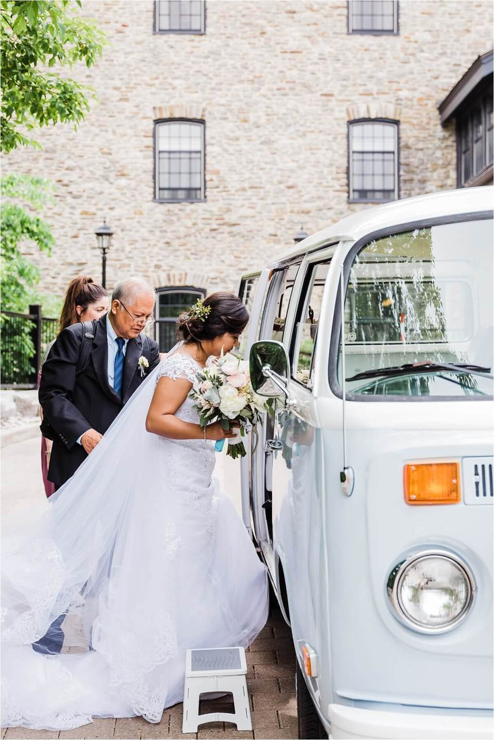 Bride getting into a VW Kombi when leaving the Old Mill Inn in Toronto Ontario during her wedding day