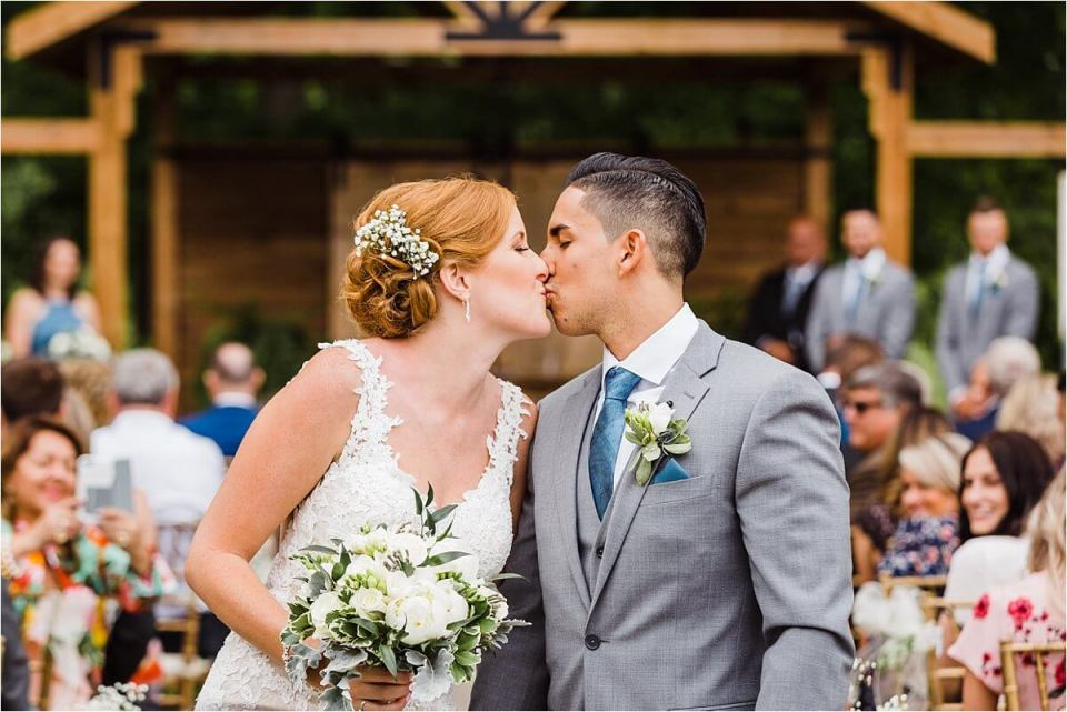 The newlywed couple kiss as they leave their outdoor ceremony at Club Roma in St Catherines Ontario