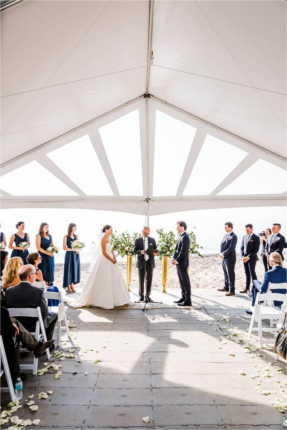Bride and groom standing at the altar during their beach tent wedding in Zurich Ontario