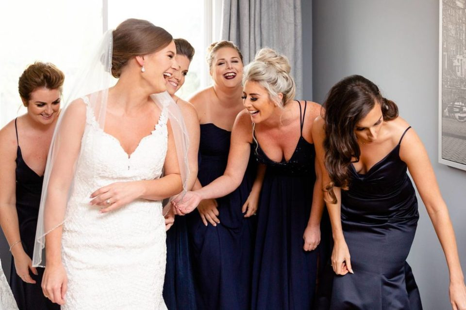 Happy laughing Hamilton Ontario Bride getting ready in her wedding dress with her bridesmaids helping her