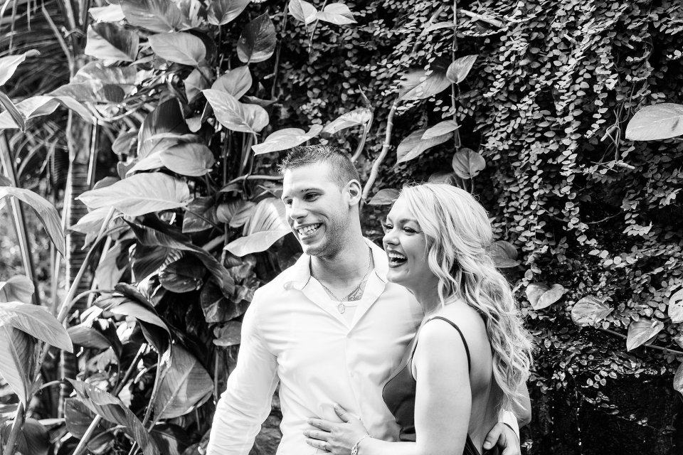 black and white photo of engaged couple laughing together