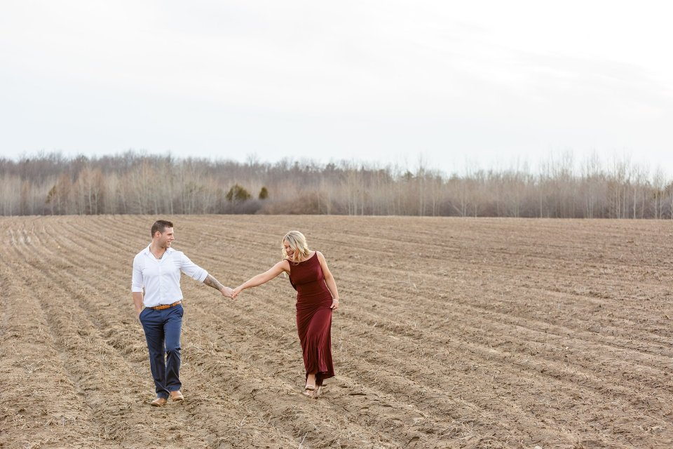 Engaged couple walking across a field playfully