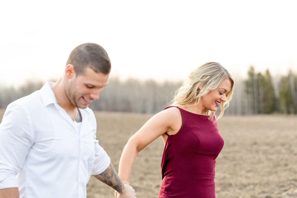 Man and woman laughing a walking across a farm field