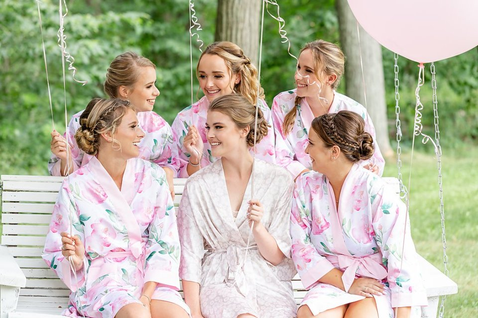 Bride with her bridesmaids in matching robes sitting on a white swing.