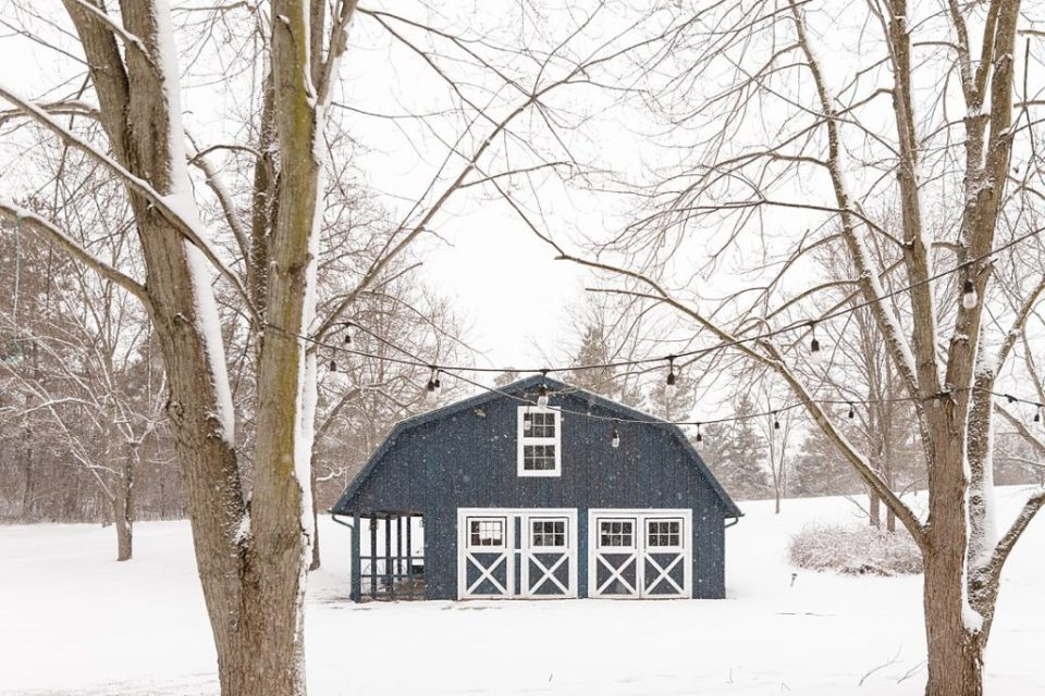 Blue barn with white barn doors at winter time