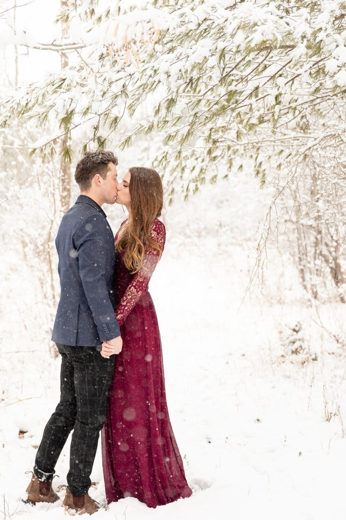 handsome man kissing a beautiful woman in a lulus lace burgundy dress at a winter engagement session