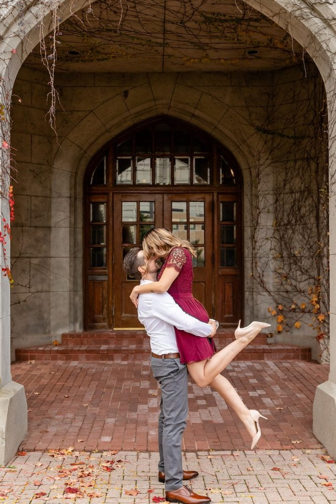 Man picking up girl in burgundy dress with red heels at the old courthouse in london ontario