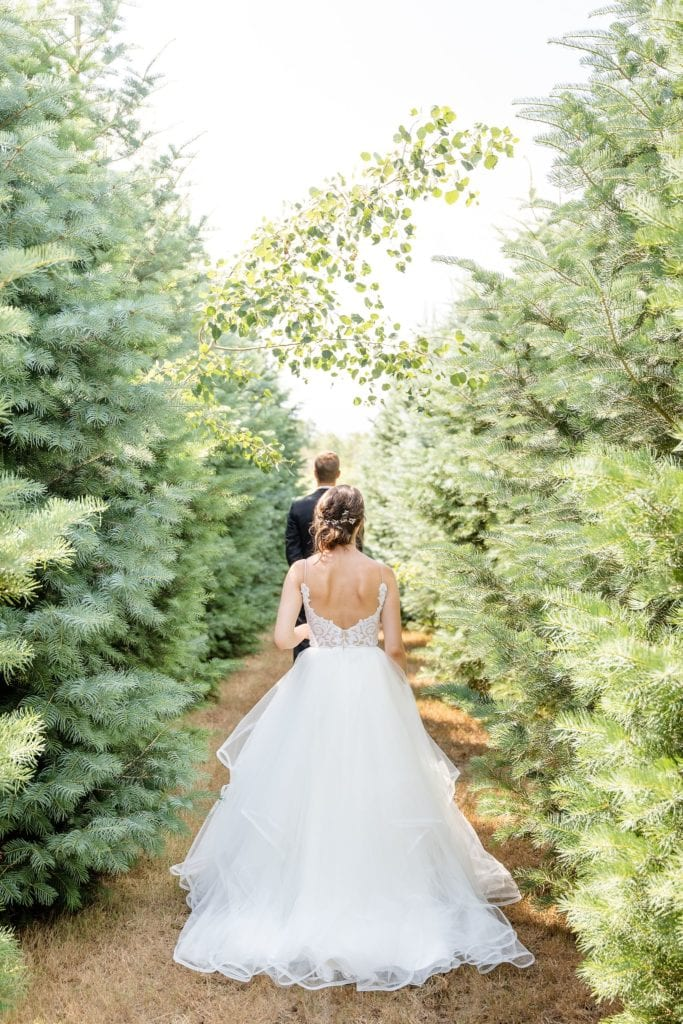 Bride walks towards her future husband during their emotional first look between the pines at arrowwood farms scaled