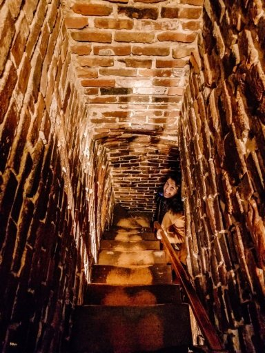 A light brown, narrow, brick stairway with a girl peeking out from the bottom